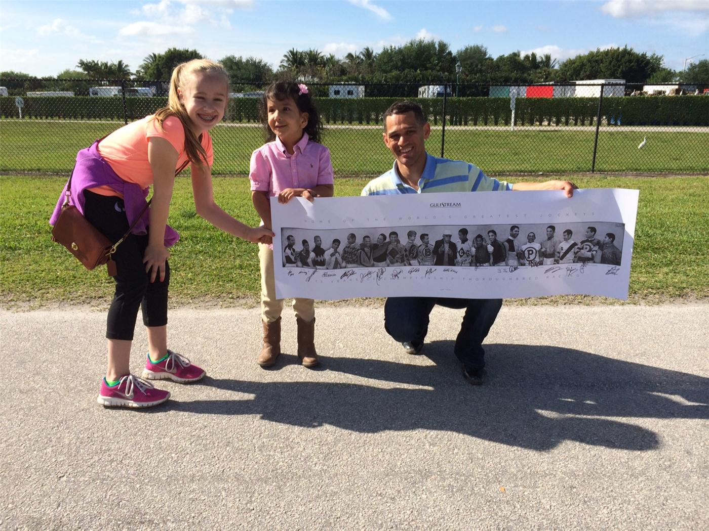 Jockey Javier Castellano gives Adison (middle) a poster autographed by the Gulfstream jockey colony